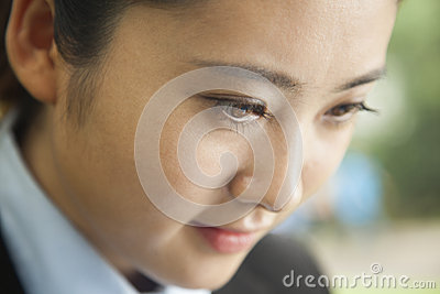 Young concentrated businesswoman s face looking down, portrait