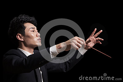 Young conductor with baton raised, black background