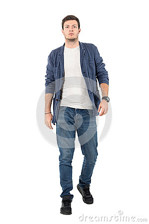 Free Young Confident Man In Denim Unbuttoned Shirt And Jeans Walking Towards Camera Stock Photo - 87124860