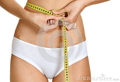 Young conscious woman measuring her waist