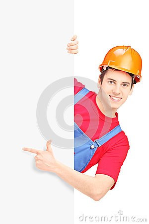 Young construction worker with helmet gesturing on a blank panel