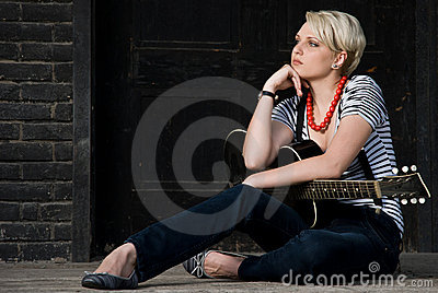 Young cool girl posing with guitar