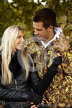 Young couple in autumn park smiling