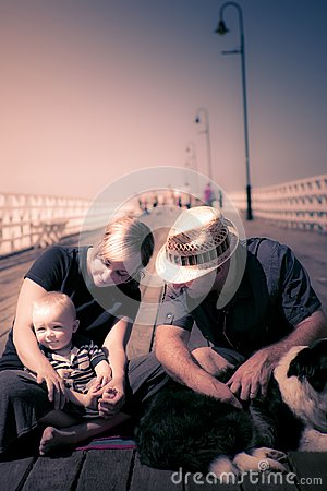 Young couple and baby boy sitting on the boardwalk