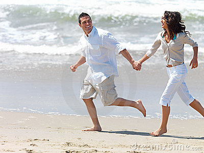 Young couple on beach, running hand in hand.