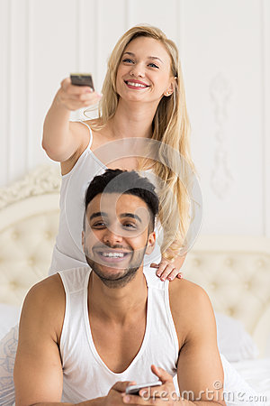 Young Couple In Bed, Happy Smile Hispanic Man And Woman Hold Console Change Channels Stock Photo