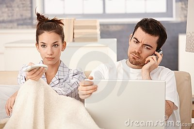 Young couple in bed man working woman watching tv