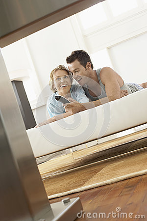 Young Couple On Bed Watching Television