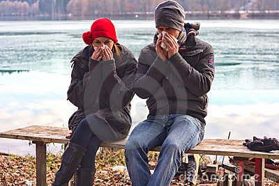 A Young Couple Blowing Their Noses