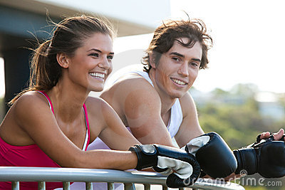 Young Couple in Boxing Gloves Leaning on Railing