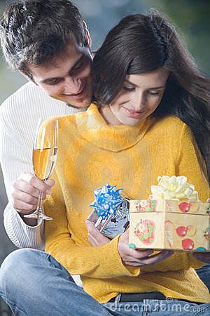 Young couple celebrating event with champagne glasses and gifts