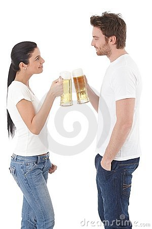 Young couple clinking with mugs of beer smiling Stock Photo