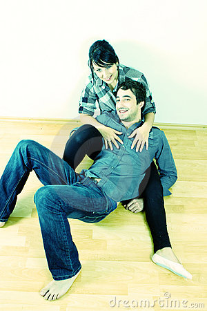 Young couple cuddling on the floor
