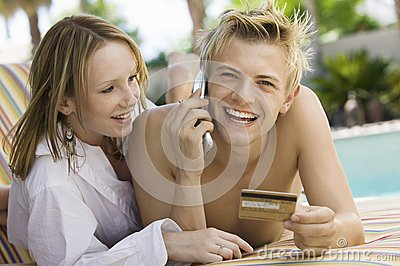 Young couple on deck chair by pool man making credit card purchase on mobile phone portrait