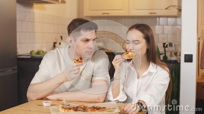 Young couple with discontent eats pizza at home stock video footage
