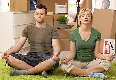 Young couple doing yoga at new house