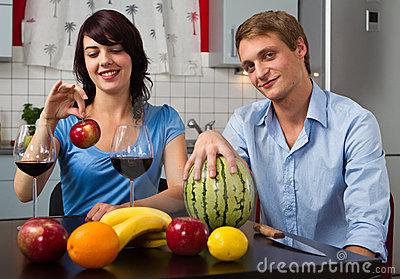 Young couple drink red wine and eat fruits