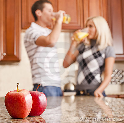 Young Couple Drinking Glass of Orange Juice