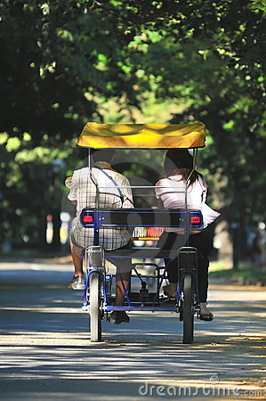 young couple driving tandem bike in park