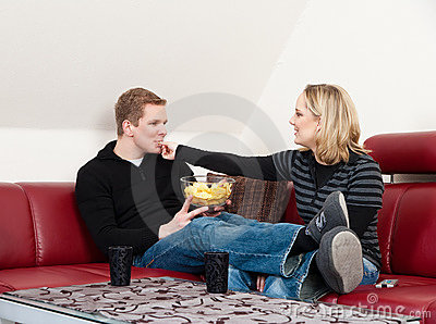 Young couple eating chips
