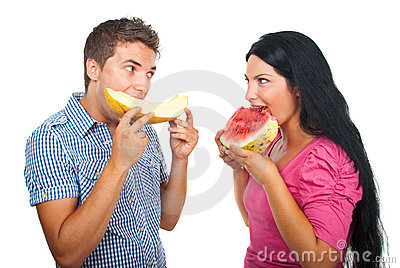 Young couple eating melon
