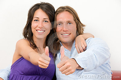 Young couple embraced with thumbs up