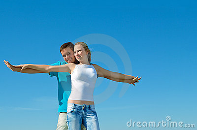 Young couple embracing against blue sky