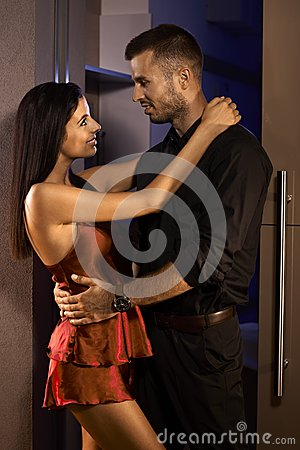 Young couple embracing in bedroom door