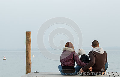 Young couple embracing dog looking at sea