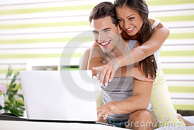 Young couple embracing and looking laptop
