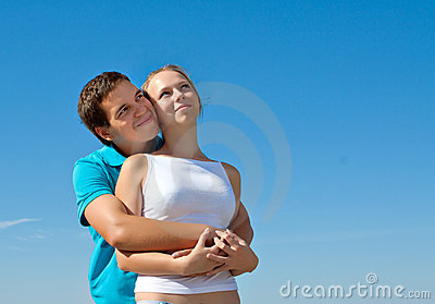 Young couple embracing and looking in the sky