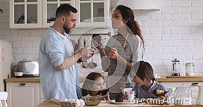Young couple enjoying fresh homemade muffins with smiling kids. Happy young couple enjoying fresh homemade muffins with smiling kids siblings in modern kitchen stock footage