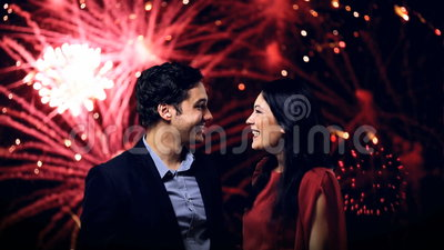 Young couple enjoying new year's eve fireworks. Front view stock video footage