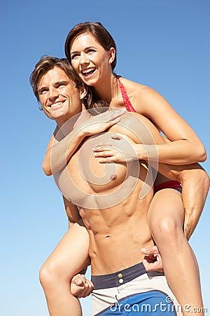 Young Couple Enjoying Piggyback On Beach Holiday