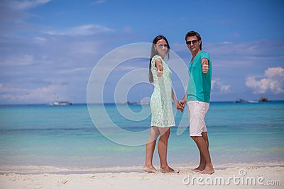 Young couple enjoying summer vacation and showing