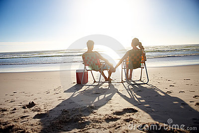 Young couple enjoying the sunset at the beach
