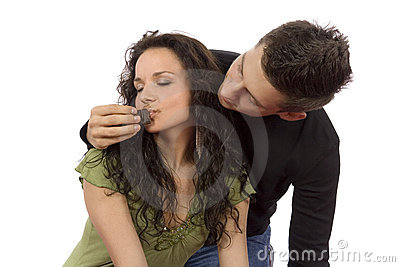 Young couple feeding each other chocolate