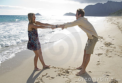 Young couple fool around on the beach