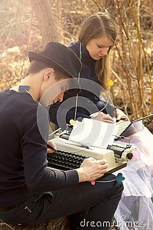 Young couple freelance typing on typewriter