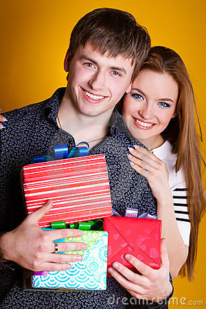 Young couple with gifts on yellow