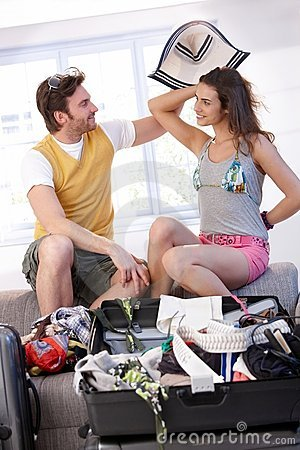 Young couple going to summer vacation packing bag