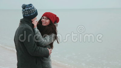Young couple in a gray winter coat, kiss against the gray sky and the sea. Winter time stock video footage