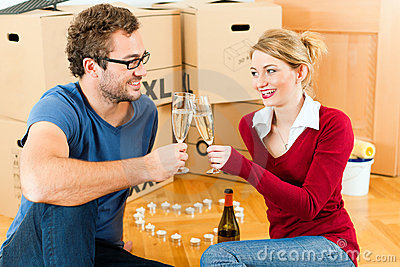 Young couple having break while moving in