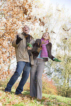 Young couple having fun with autumn leaves