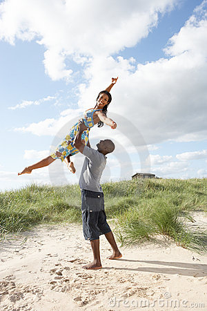 Young Couple Having Fun In Dunes By Beach