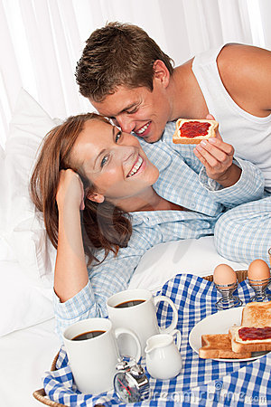 Young couple having home made breakfast in bed