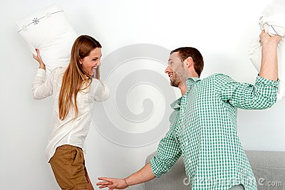 Young couple having pillow fight.