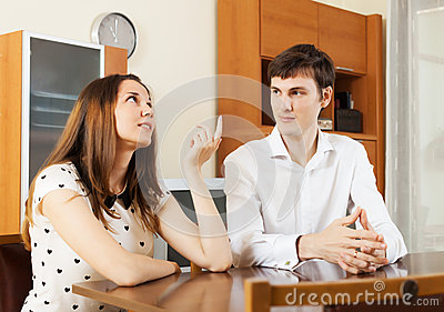 Young couple having serious talking at table