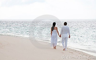 Young couple having a walking on the sea shore