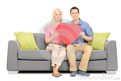 Young couple holding big red heart seated on sofa